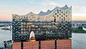 The Elbphilharmonie consists of a spectacular marquee-like glass structure mounted on top of a former warehouse with a brick-facade.